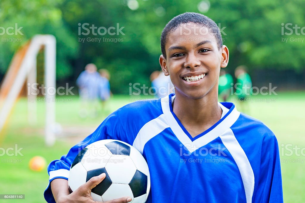 Excited male teenage soccer player stock photo