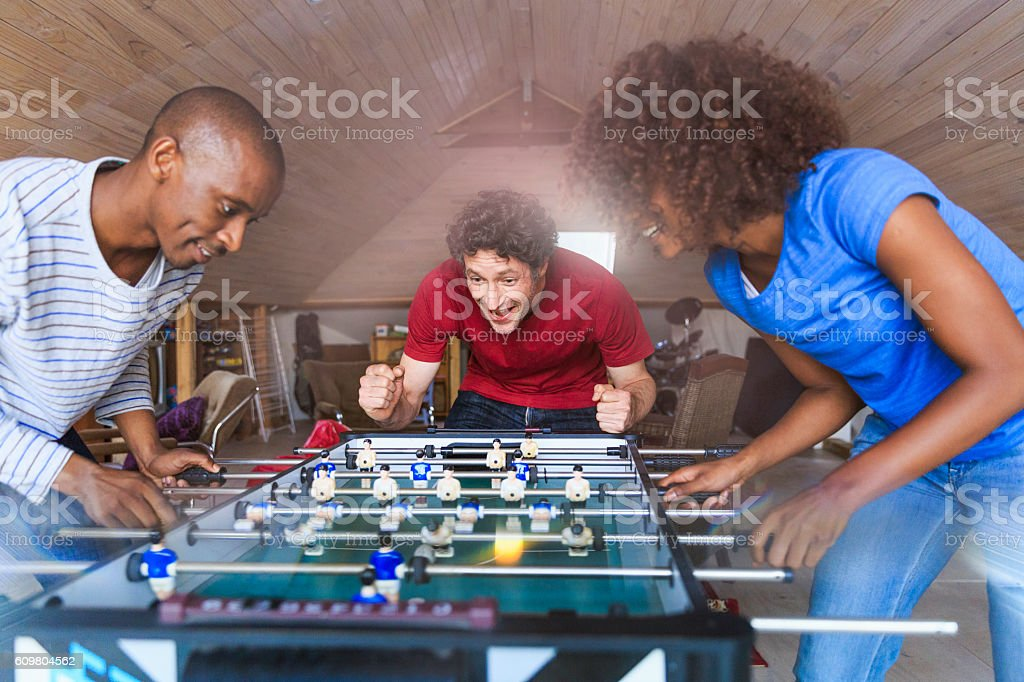 Excited man cheering for friends playing foosball stock photo