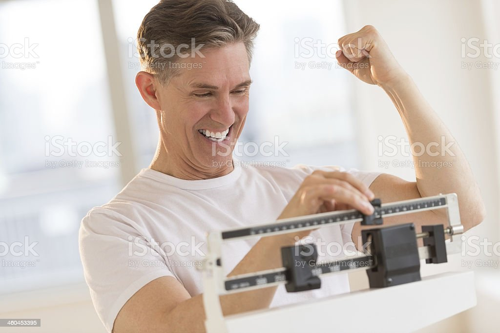 Excited Man Clenching Fist While Using Weight Scale stock photo