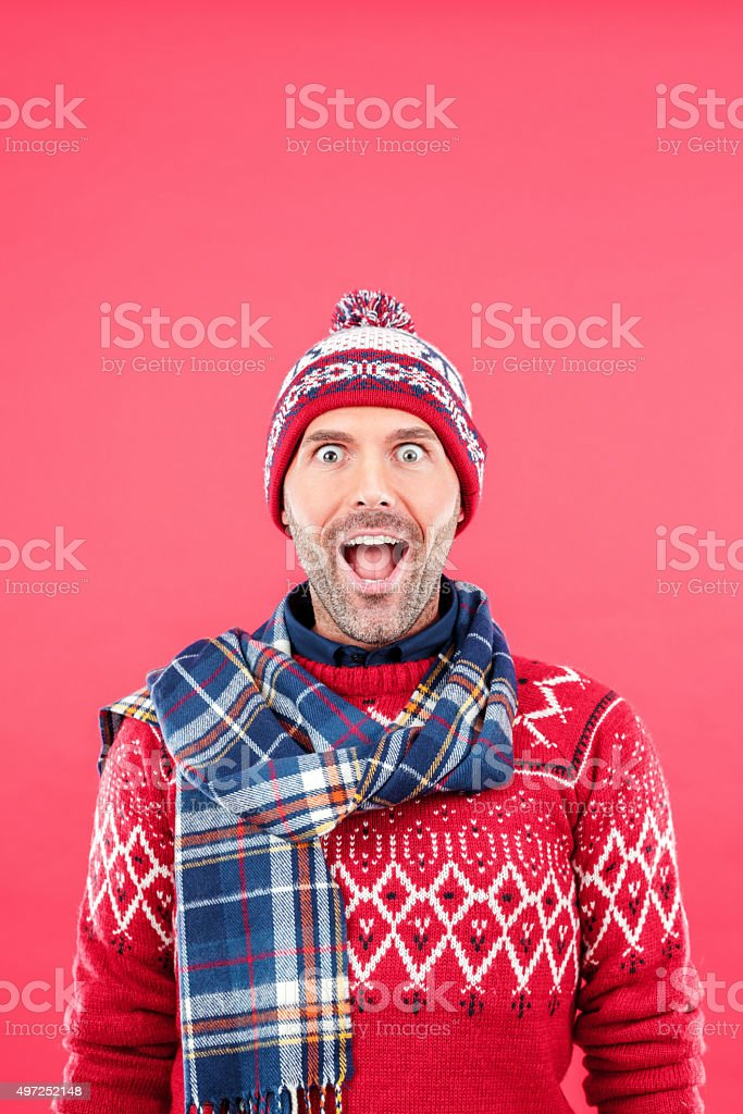 Excited man in winter outfit against red background stock photo