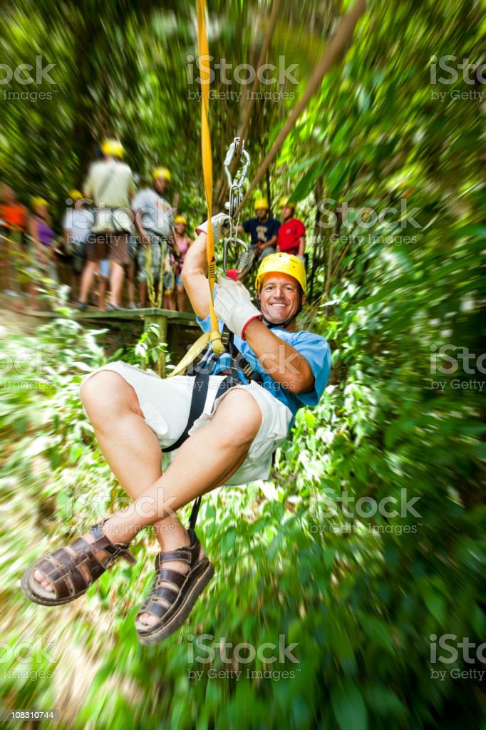 Excited man in-motion on zipline in tropical jungle rainforest stock photo