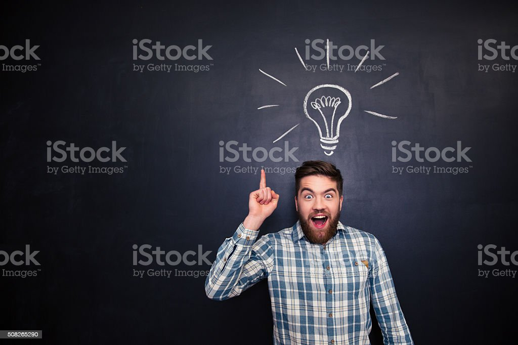 Excited bearded young man in checkered shirt pointing up over...