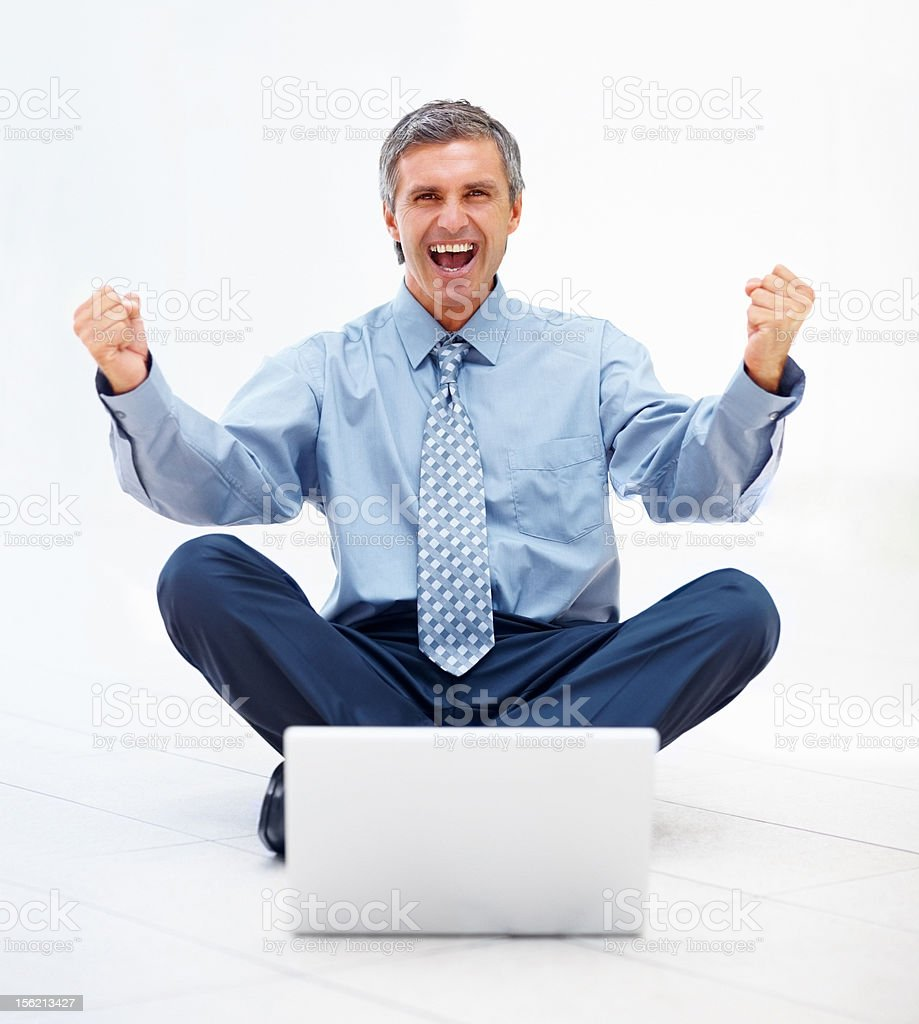 Excited mature businessman with laptop royalty-free stock photo