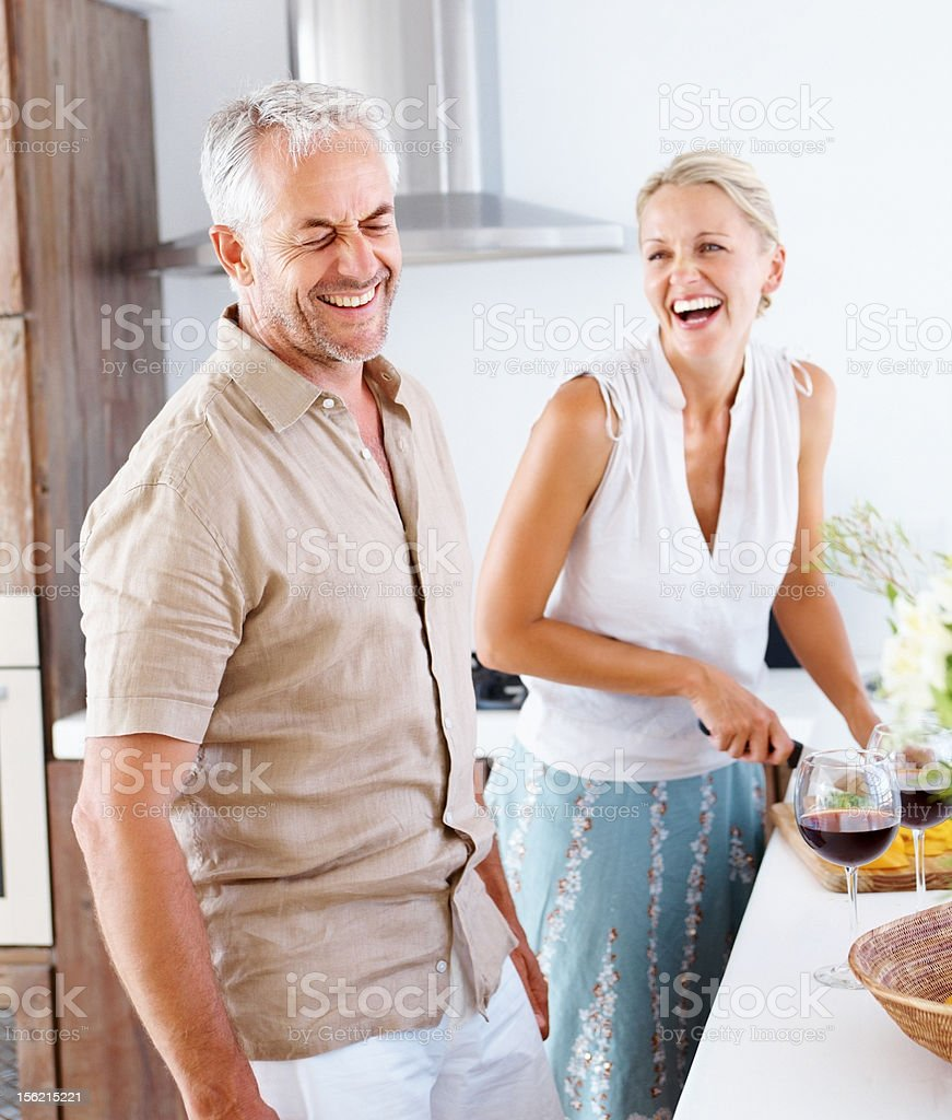 Excited mature couple preparing food in kitchen royalty-free stock photo