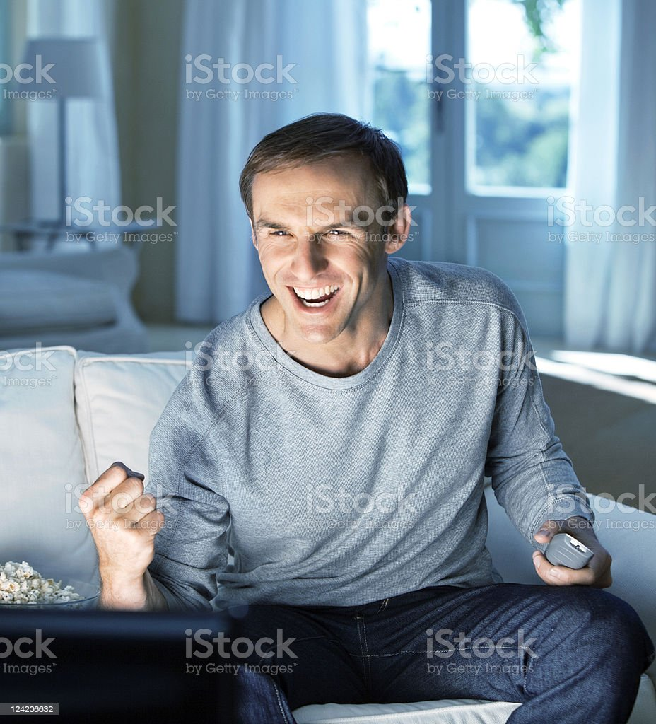 Excited mid adult man enjoying television royalty-free stock photo