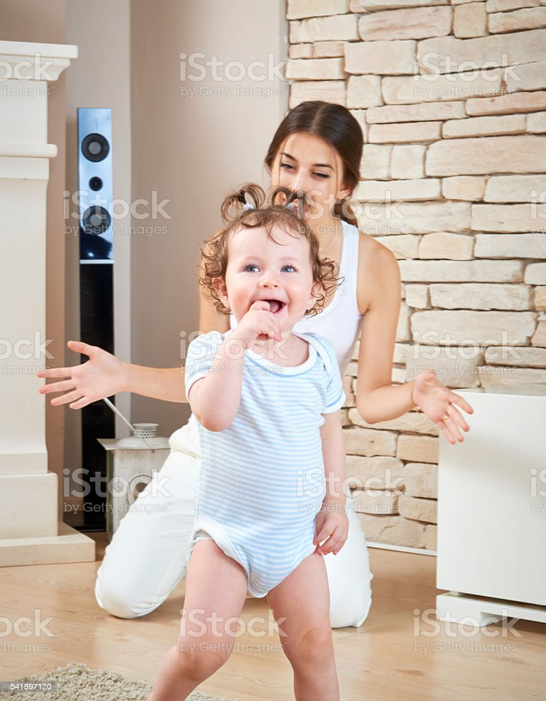 Excited Mother Watching Baby Take Her First Steps stock photo