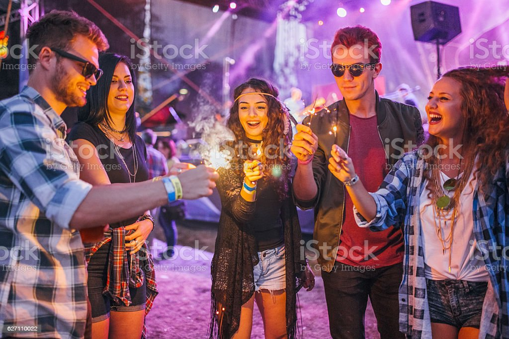 Group of friends dancing and celebrating with sparklers at music...