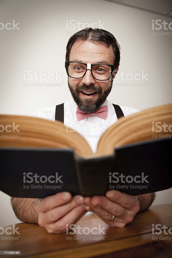 Excited Nerd Guy Sitting at Old School Desk Reading Book royalty-free stock photo