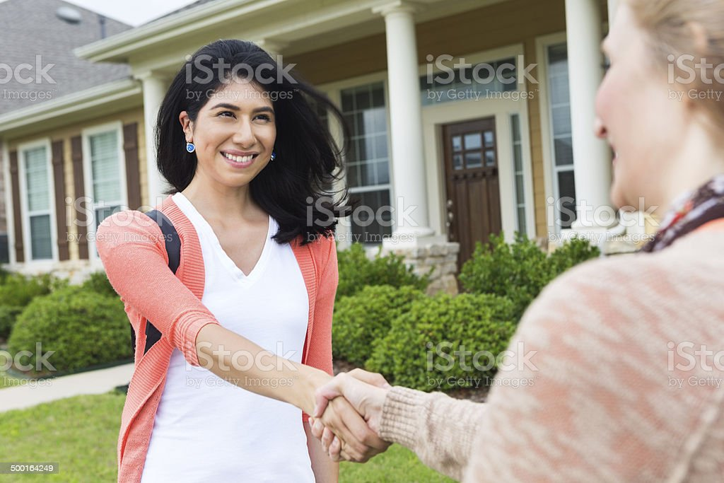 Excited new female homeowner shanking hands with realtor stock photo