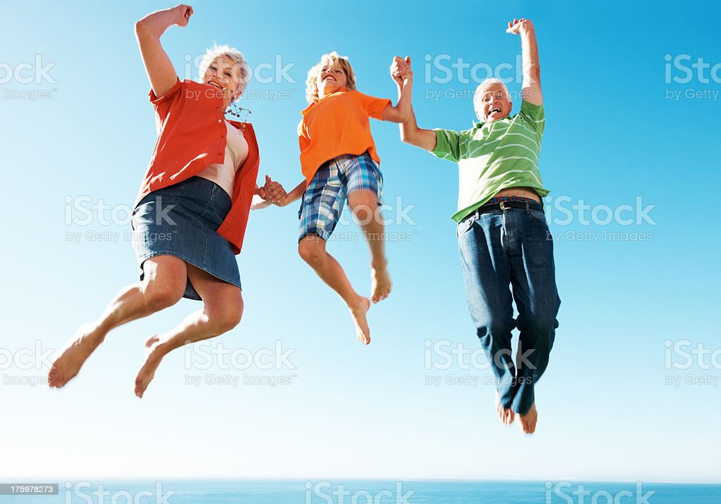 Excited old couple jumping in air with little boy stock photo