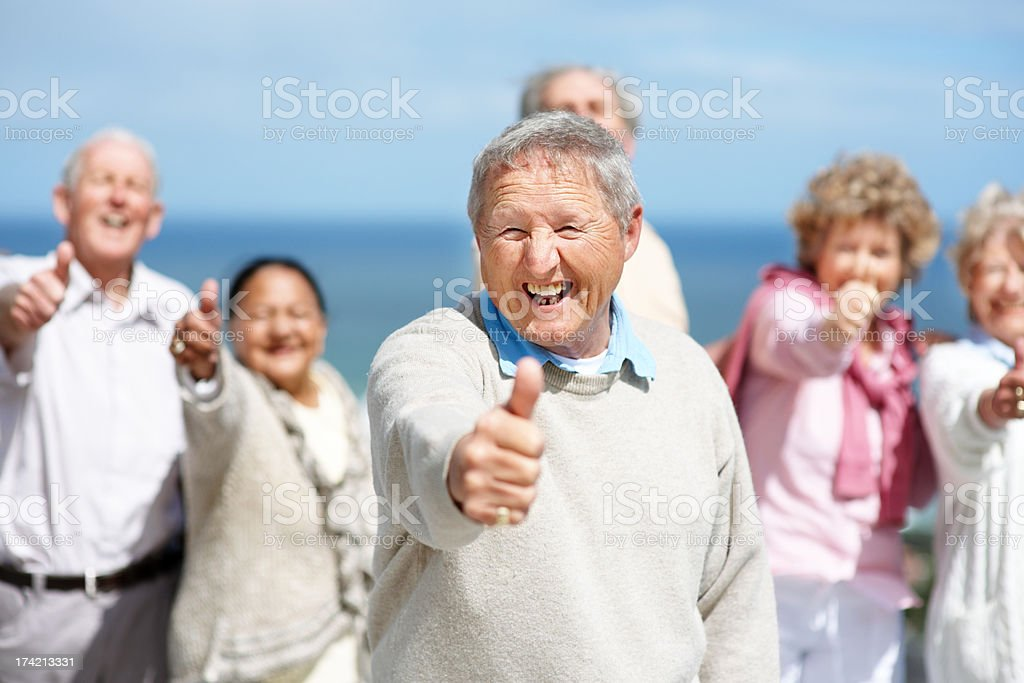 Excited old man showing thumbs up sign with his friends stock photo