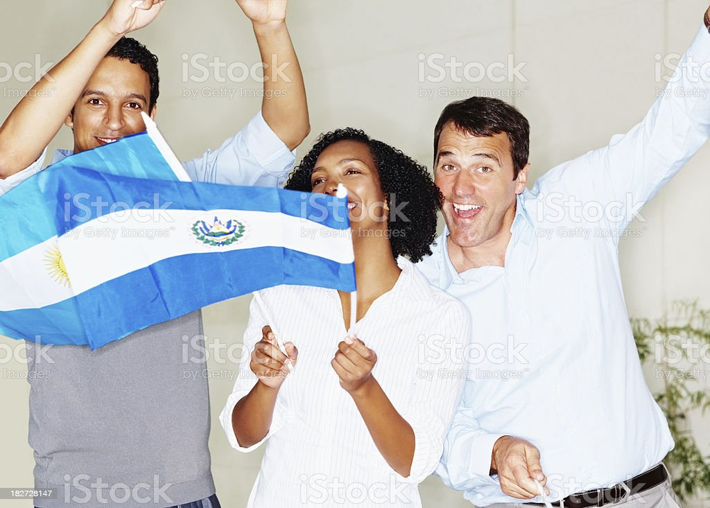 Excited people dancing and waving flags while looking at you stock photo