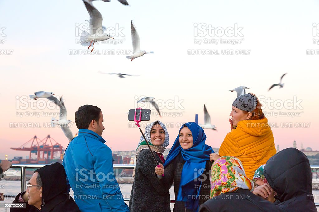 Excited People feeding Sea Gulls chasing Ferry Boat stock photo
