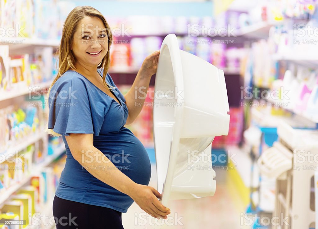 Excited pregnant woman smiles, choosing a baby bath in store stock photo