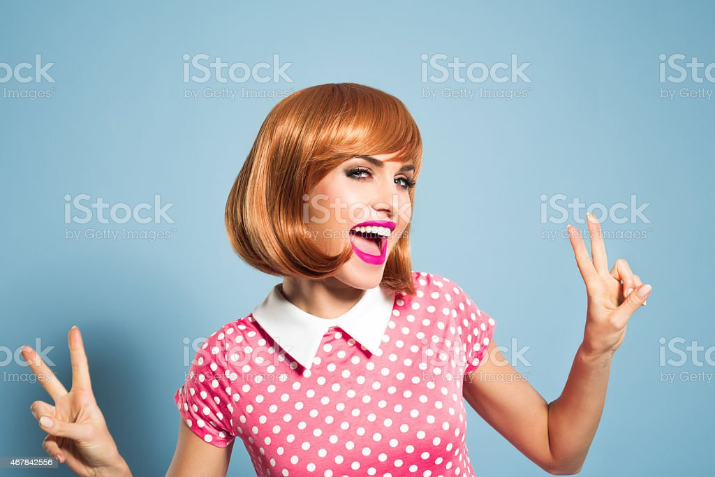 Excited red hair young woman wearing polka dot dress stock photo