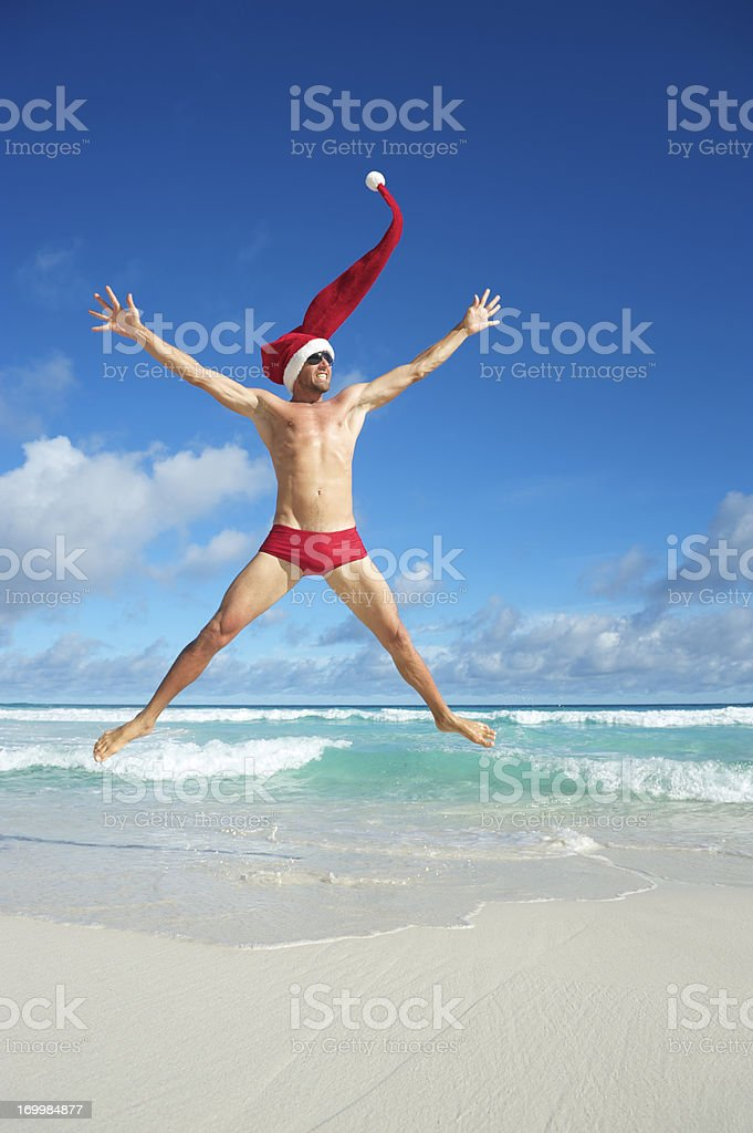 Excited Santa Hat Man Jumping for Christmas on Tropical Beach stock photo