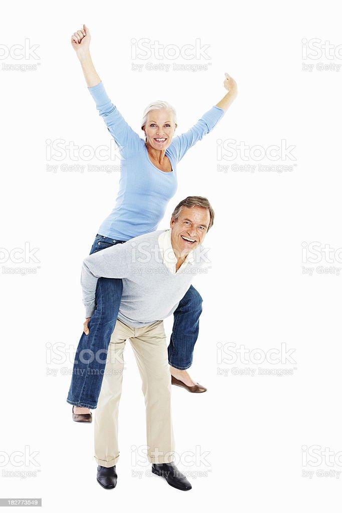 Excited senior couple enjoying a piggyback ride against white royalty-free stock photo