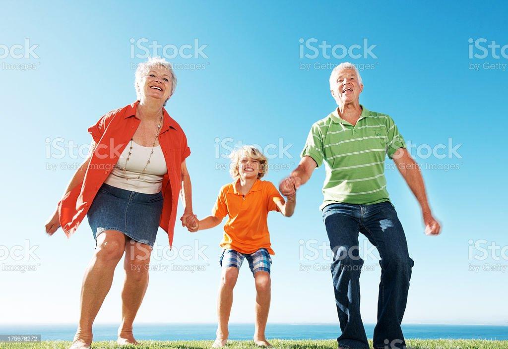 Excited senior couple enjoying holidays with their grandson stock photo