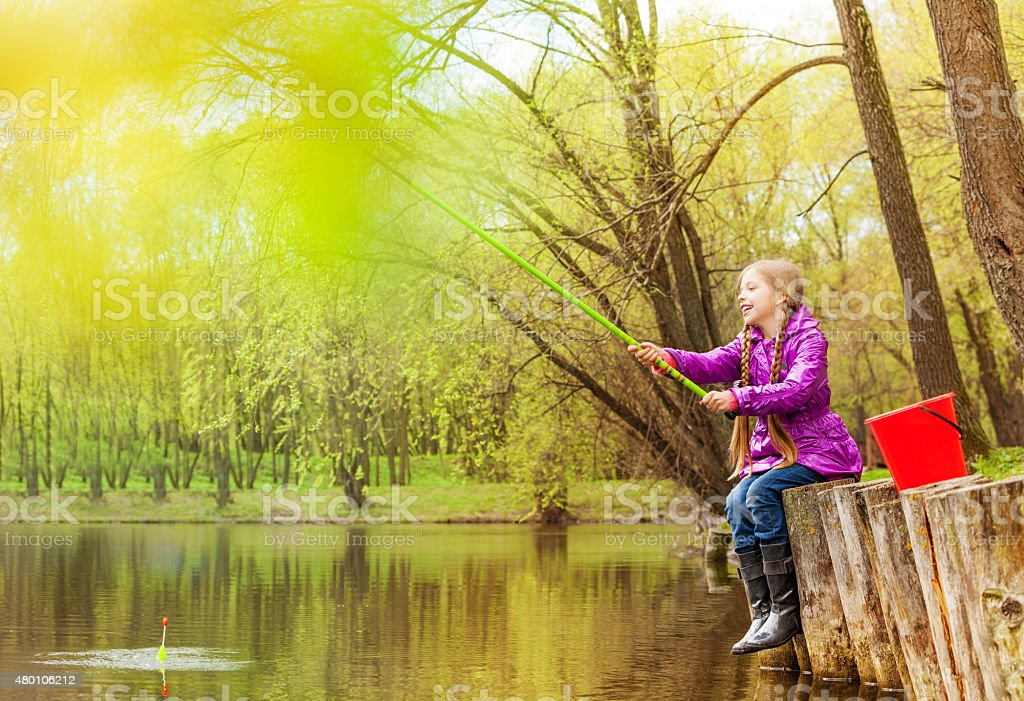 Excited small girl fishing near beautiful pond stock photo