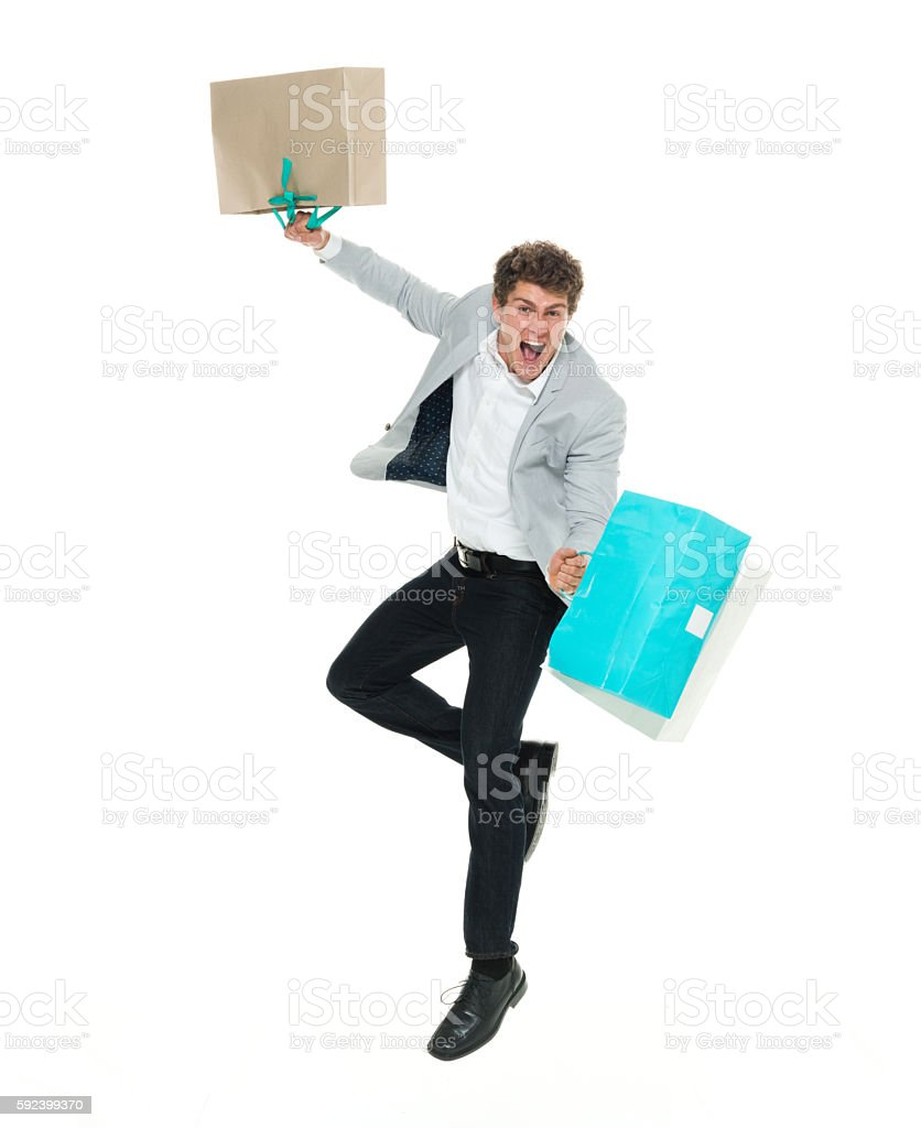Excited smart casual man jumping with shopping bag stock photo