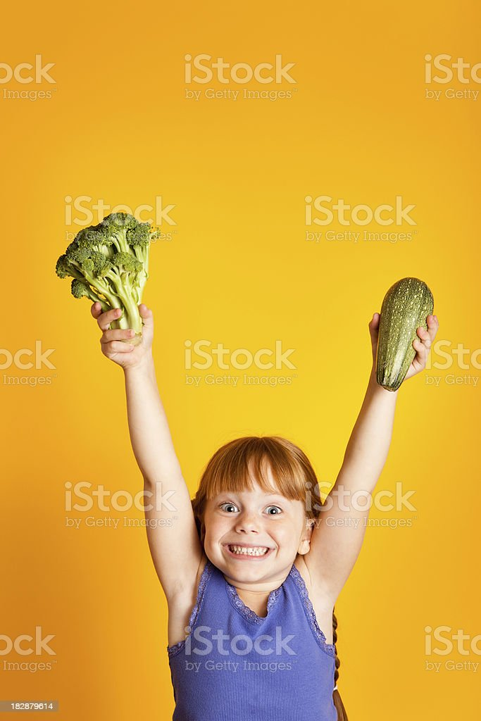 Excited, Smiling Girl Holding Up Broccoli and Zucchini royalty-free stock photo