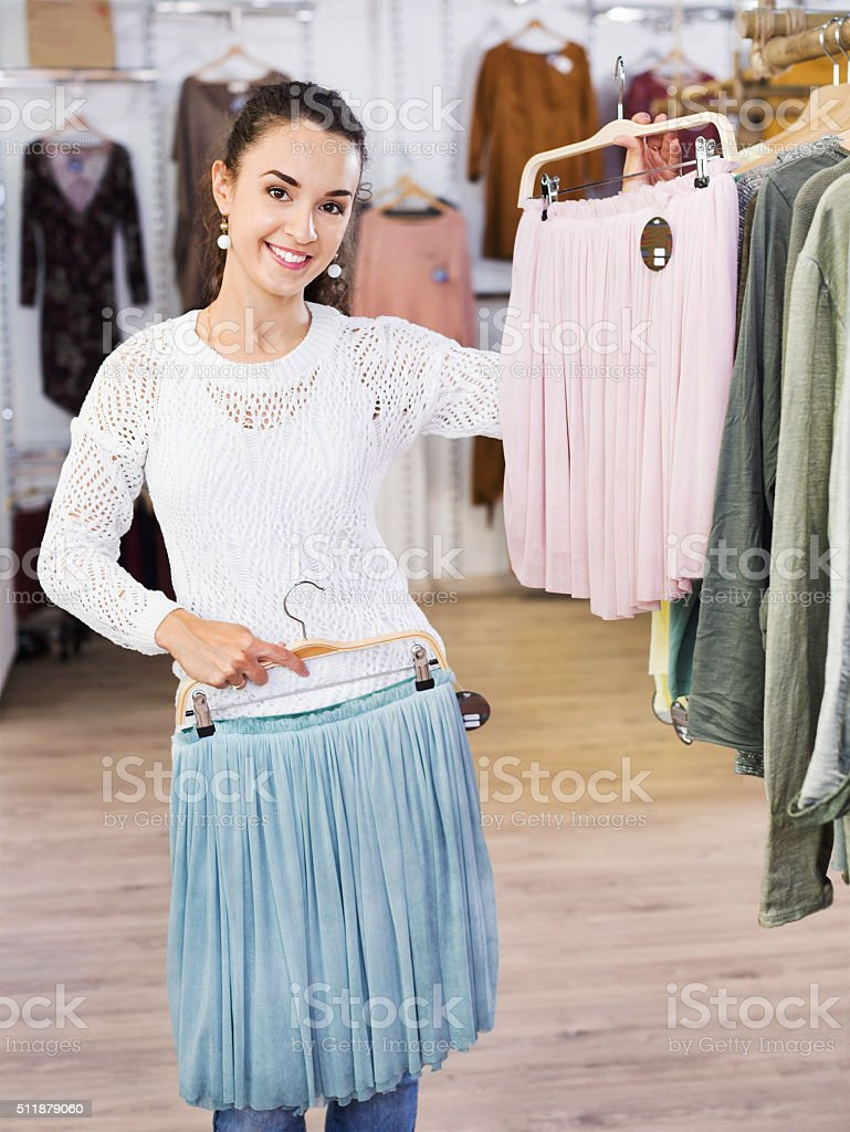 Excited smiling young woman shopping skirts stock photo