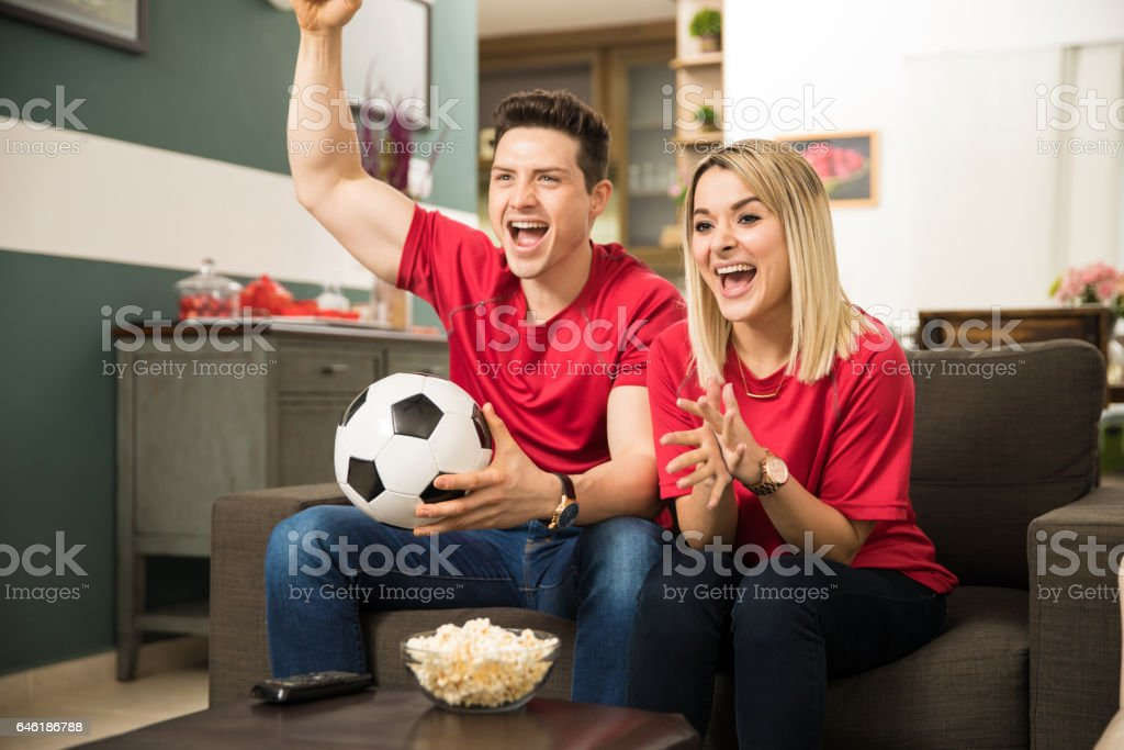Excited soccer fans watching game stock photo