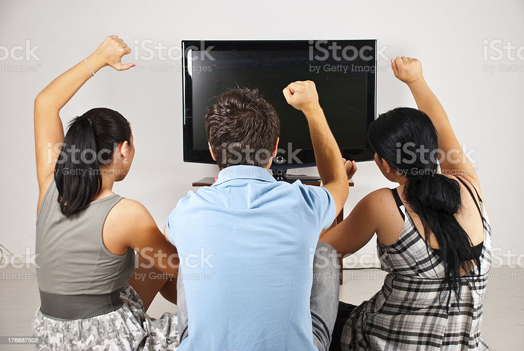 Excited soccer fans watching tv royalty-free stock photo