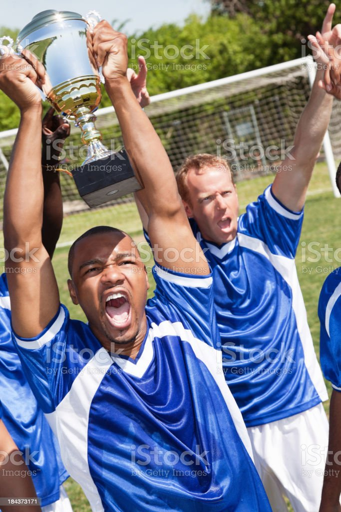 Excited Soccer Team Celebrating With Trophy After Big Win royalty-free stock photo