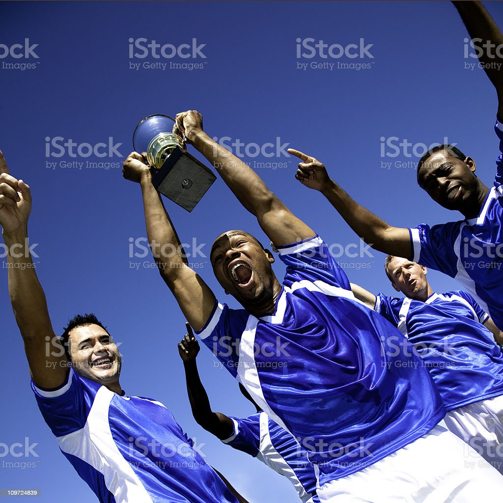 Excited Soccer Team With Trophy Celebrating Win royalty-free stock photo