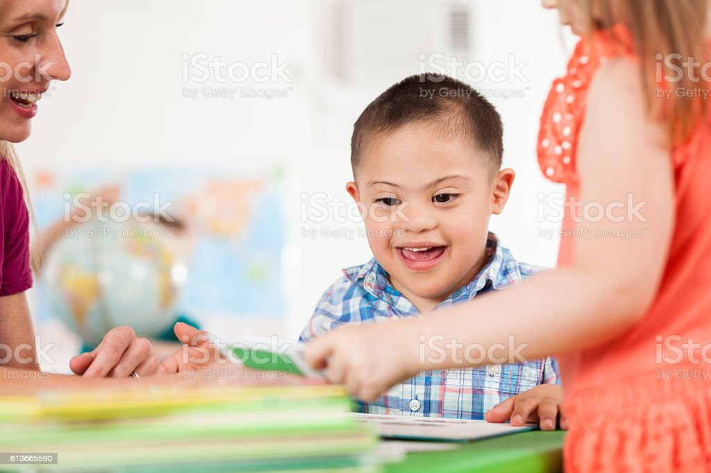Excited special needs little boy plays in preschool class stock photo