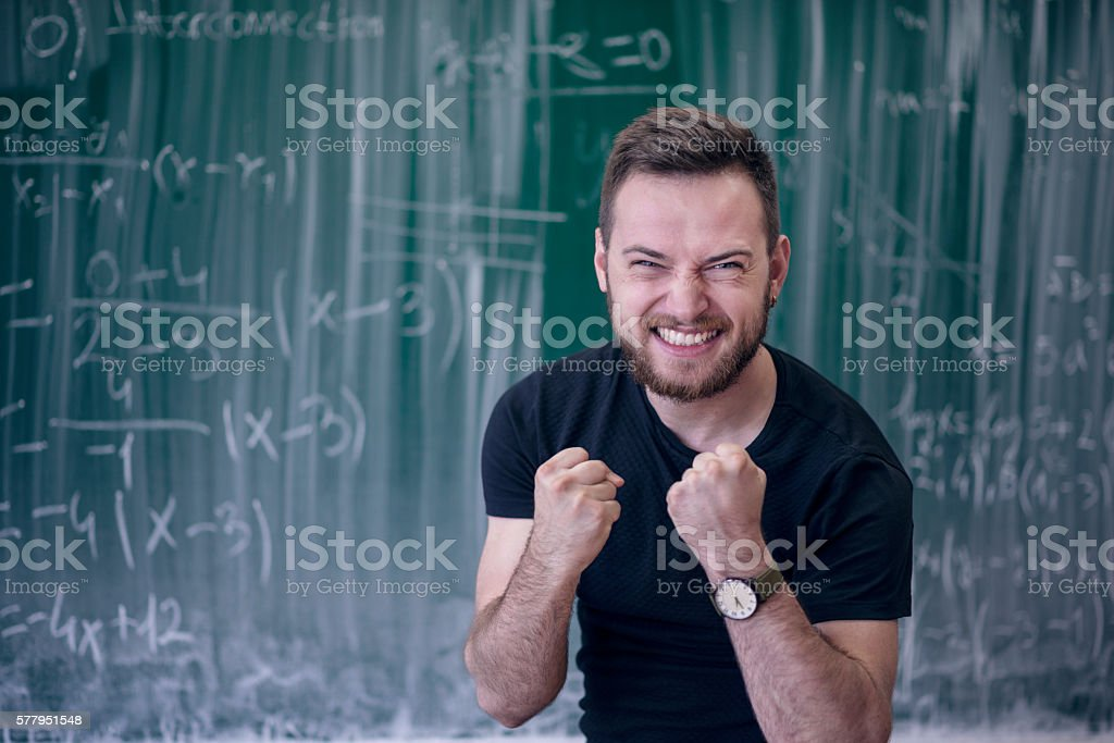 Excited Student With Clenched Fists in Front of Blackboard stock photo