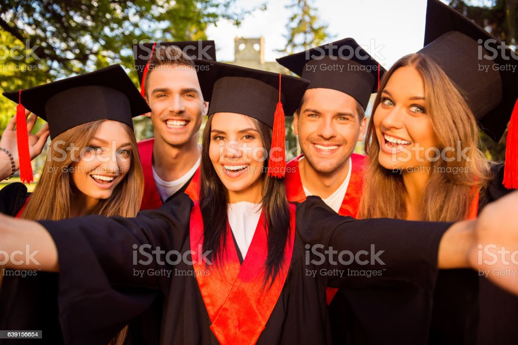 excited successful happy  graduates in robes and hats making selfie stock photo