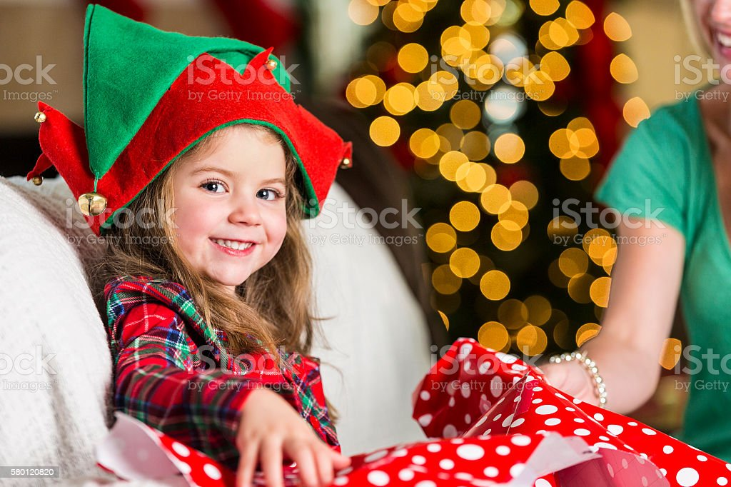 Excited sweet girl opens gift on Christmas morning stock photo