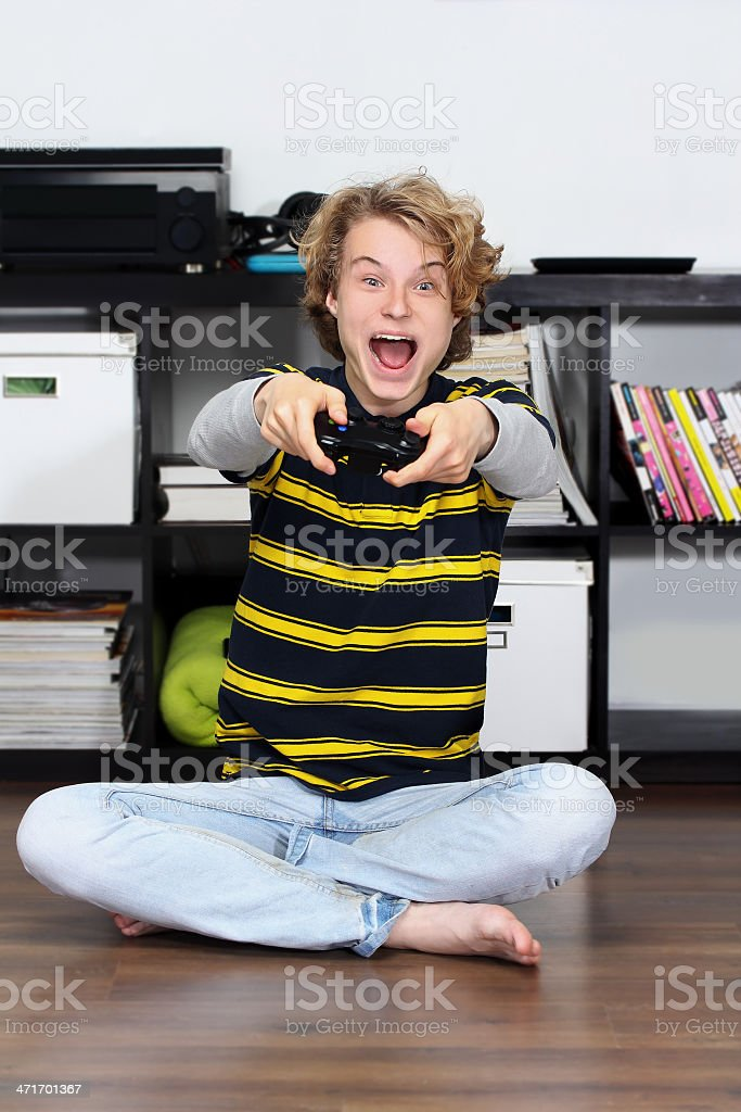 Excited teenage boy playing game, pumps his fist.Winner royalty-free stock photo