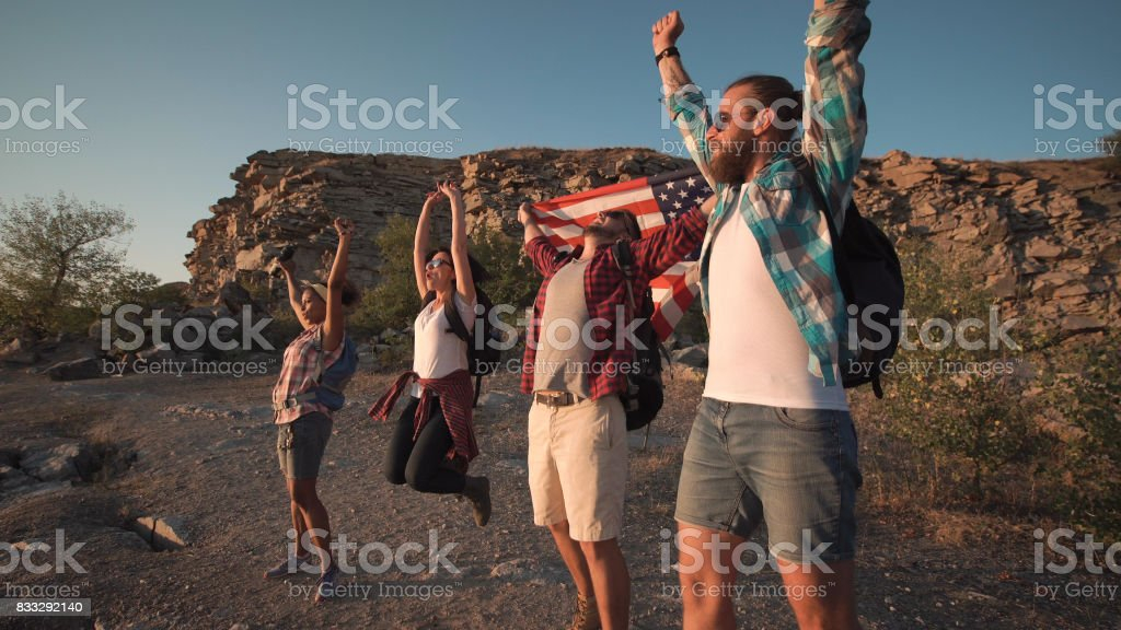 Excited travelers posing with flag stock photo