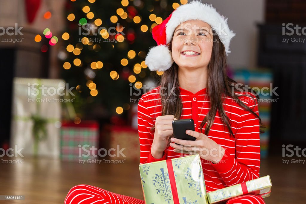 Excited tween girl receives cell phone as Christmas gift stock photo