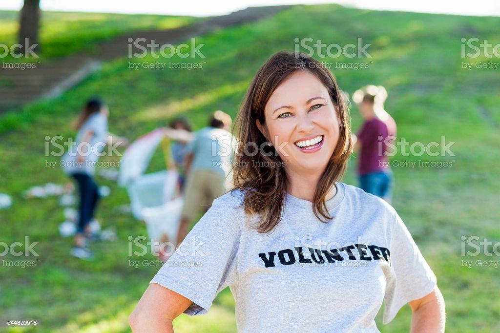 Excited volunteer picks up garbage in park stock photo