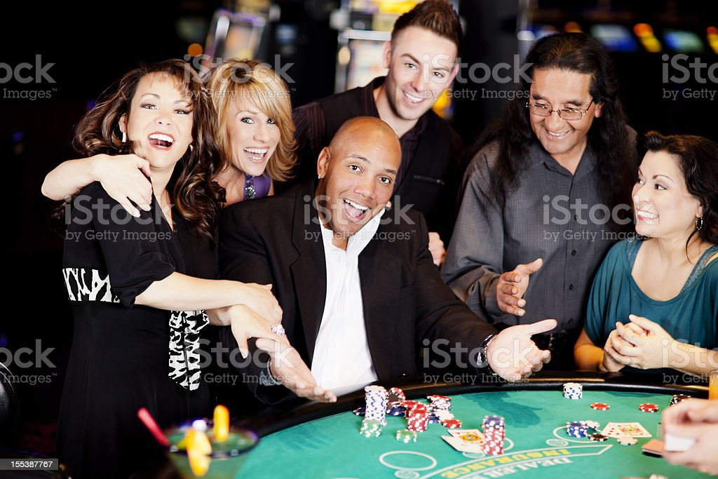 Excited winner with friends at the blackjack table stock photo