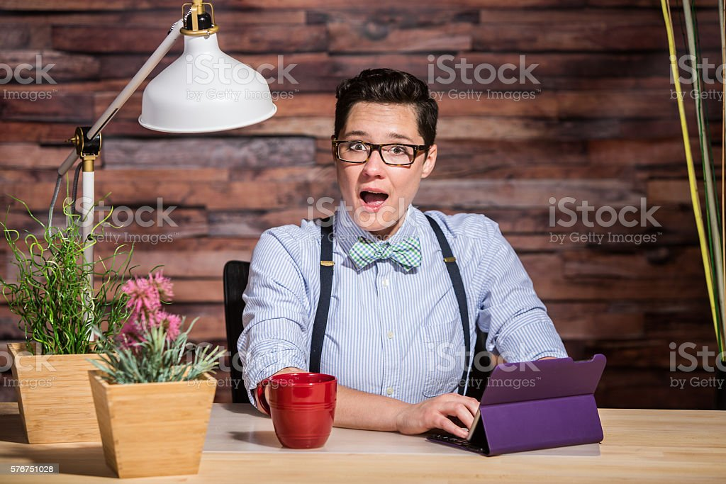 Excited Woman at Desk with Tablet stock photo
