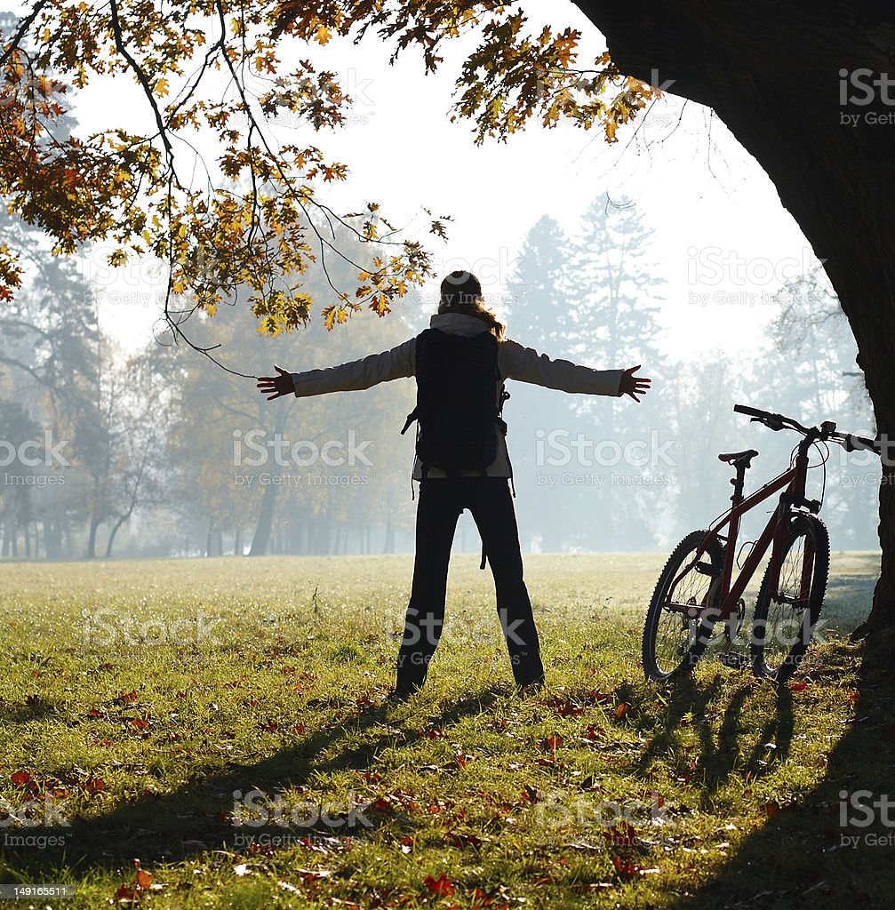 Excited woman cyclist standing in a park with hands outstretched royalty-free stock photo