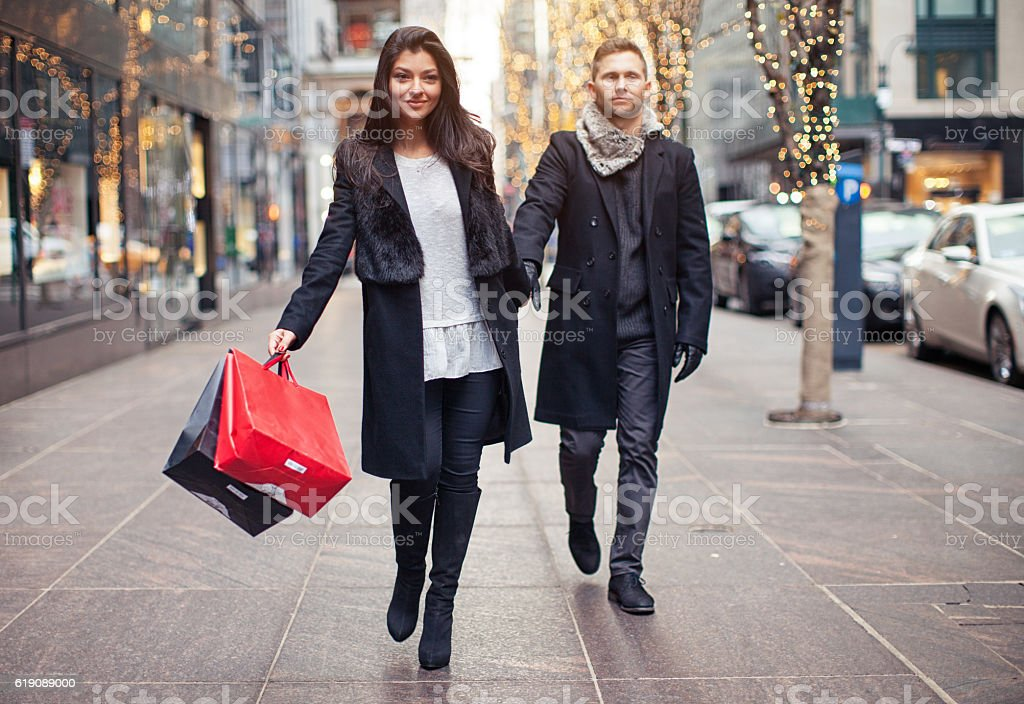 Excited woman going shopping with sad husband stock photo