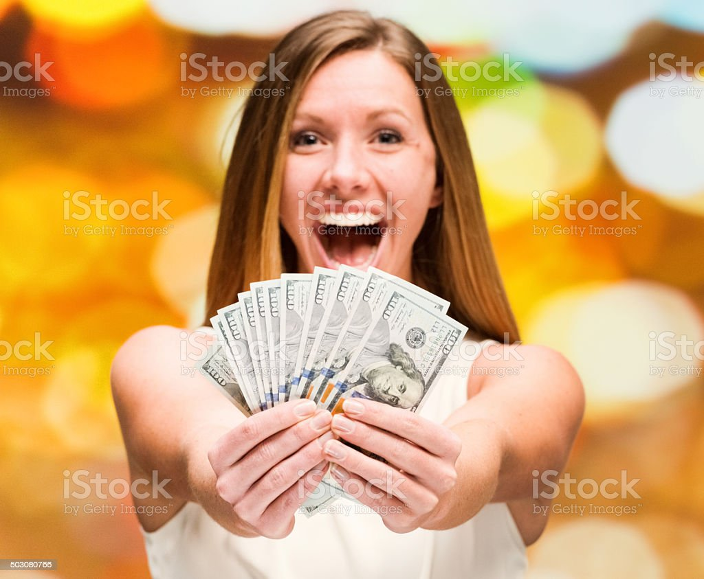 Excited woman holding money stock photo