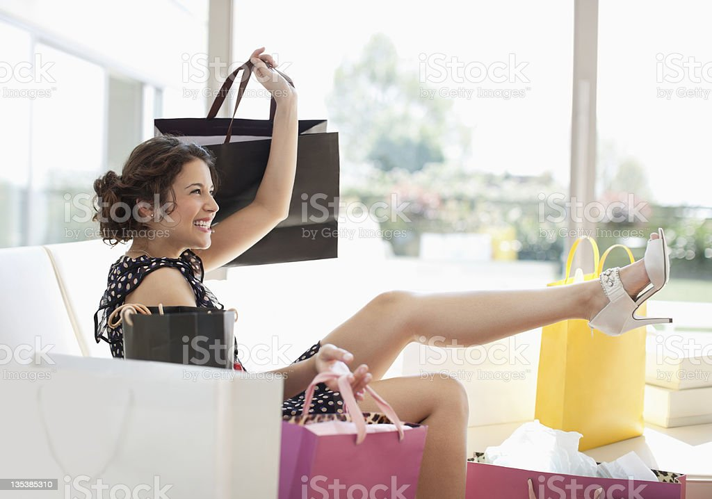 Excited woman in living room with shopping bags stock photo
