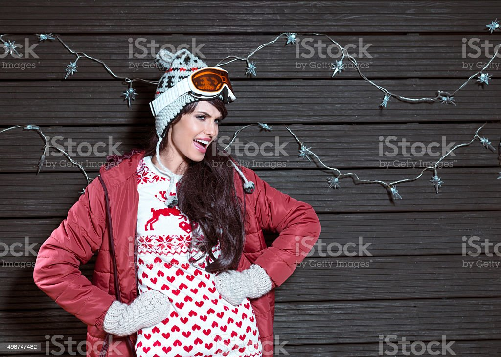 Excited woman in winter outfit, wearing puffer jacket and goggle stock photo