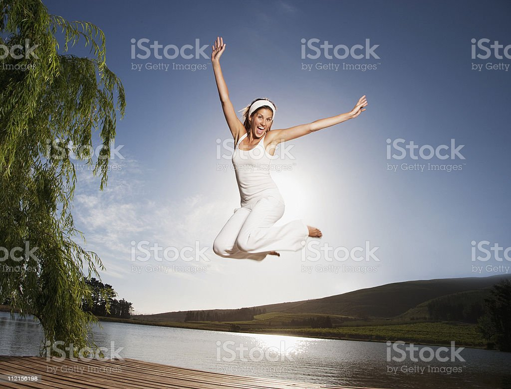Excited woman jumping on pier stock photo