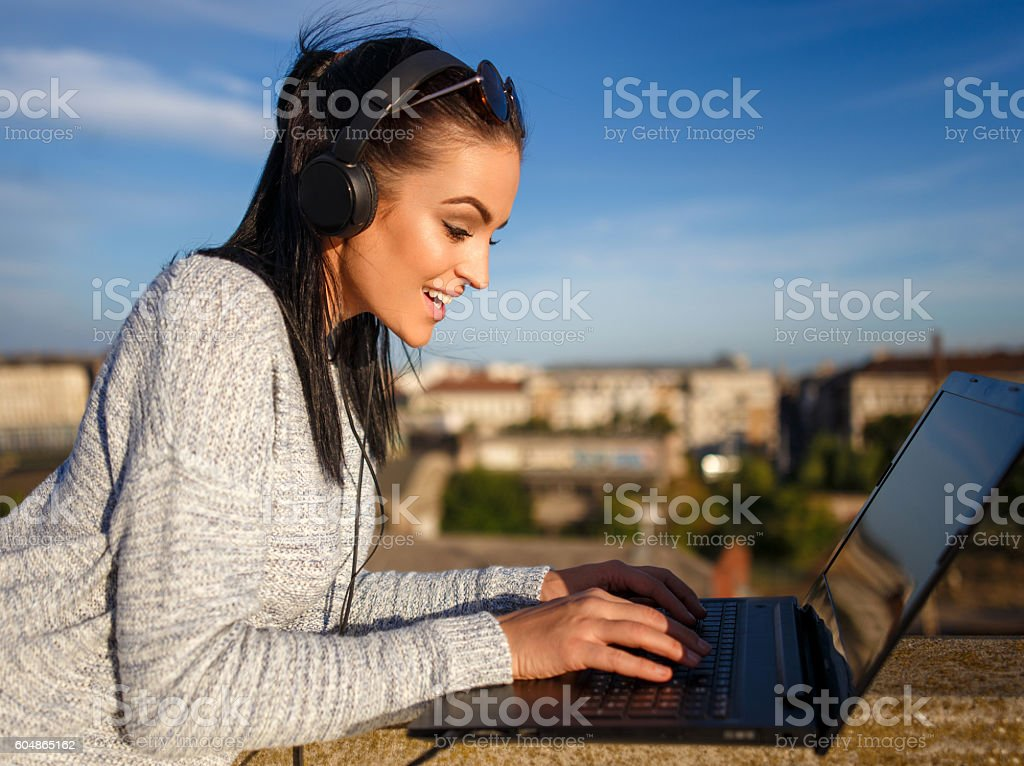 Excited woman listening music and typing on laptop outdoor stock photo