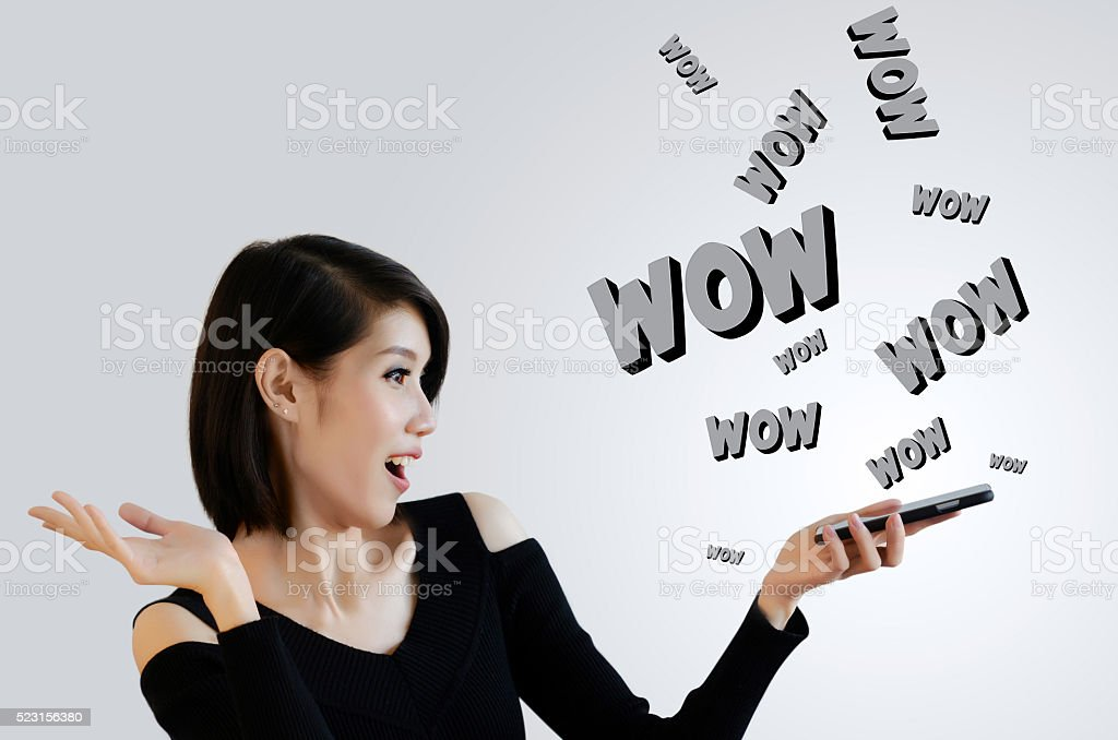 Excited woman looking at cellphone and WOW words stock photo
