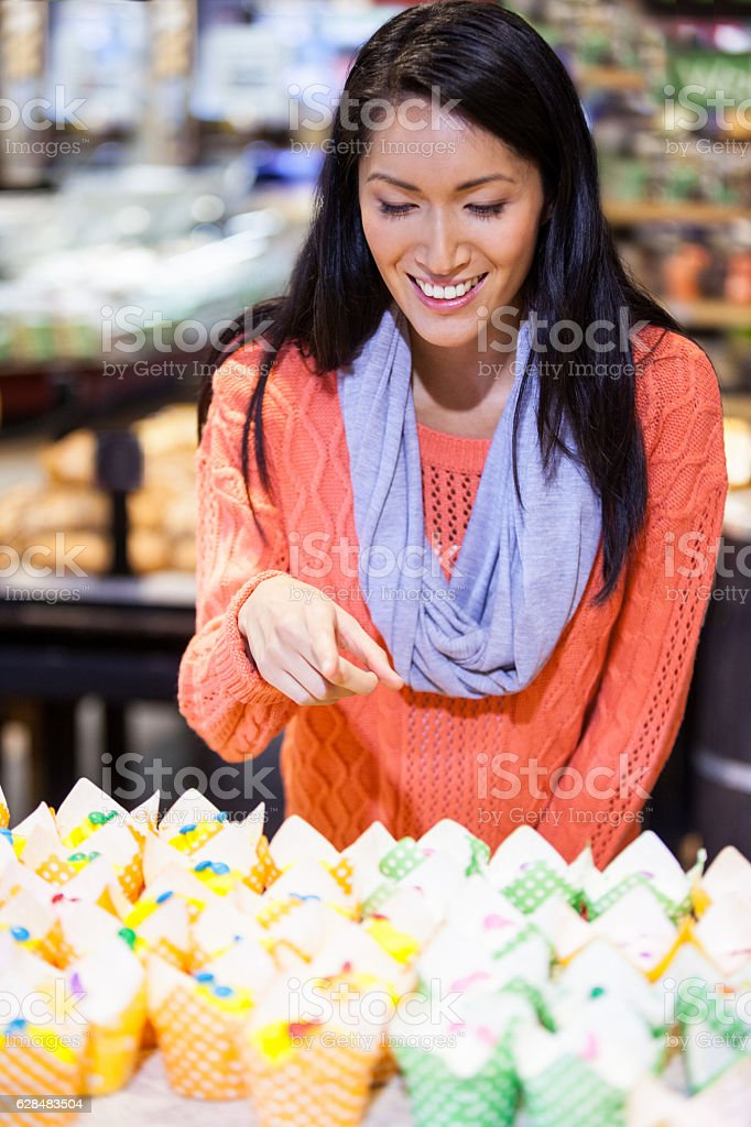 Excited woman looking at cupcakes stock photo