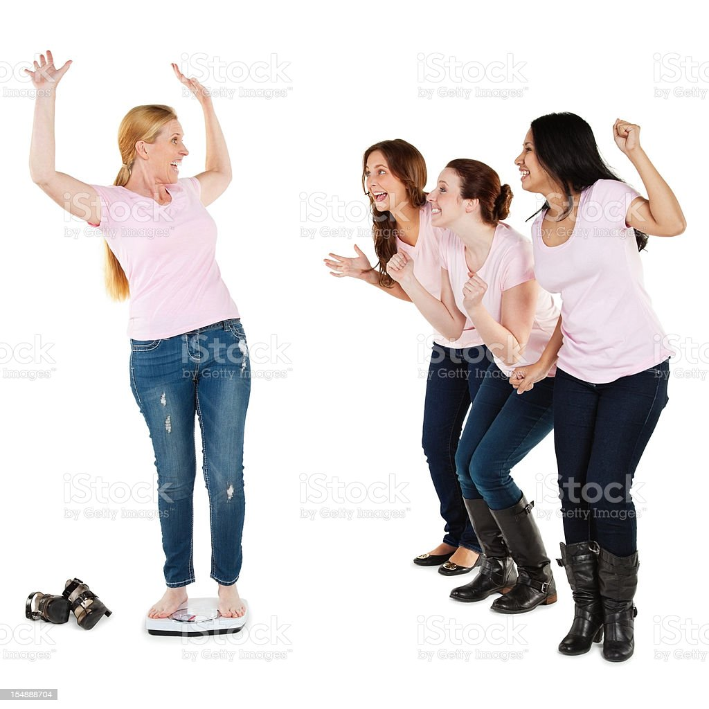 Excited Woman on Scale Encouraged By Her Friends royalty-free stock photo